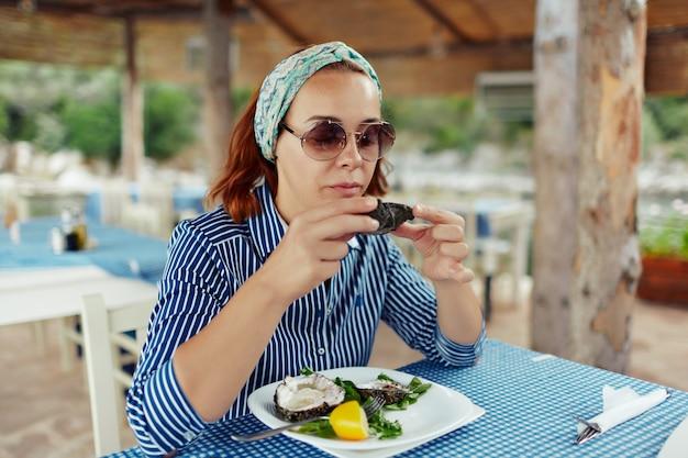 Mulher jovem, comer, ostra, em, um, restaurante ao ar livre
