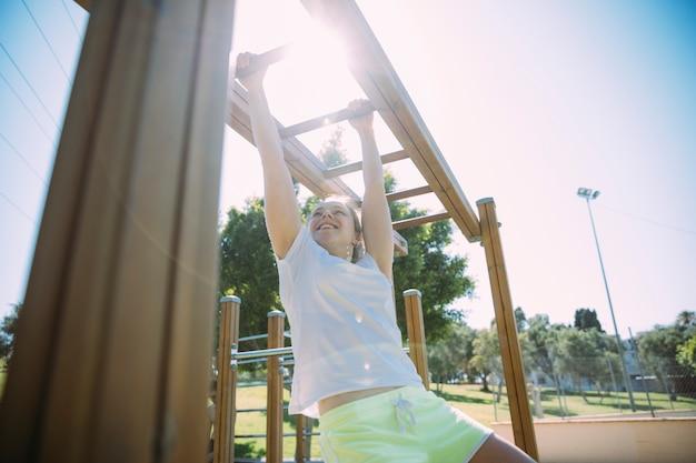 Mulher jovem competitiva exercitando em barras de macaco