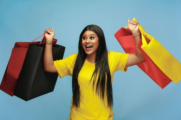 Mulher jovem comprando pacotes coloridos na parede azul