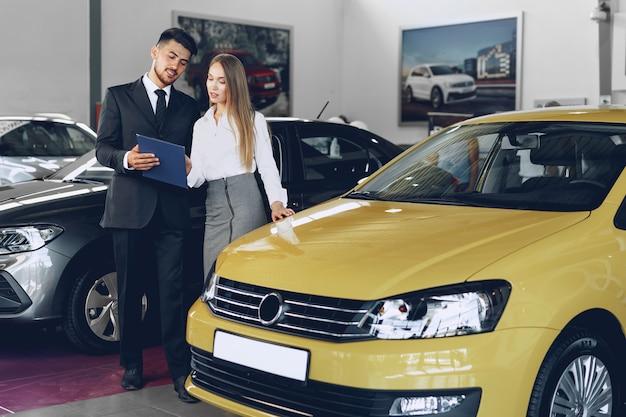 Mulher jovem comprando um carro novo no salão de beleza