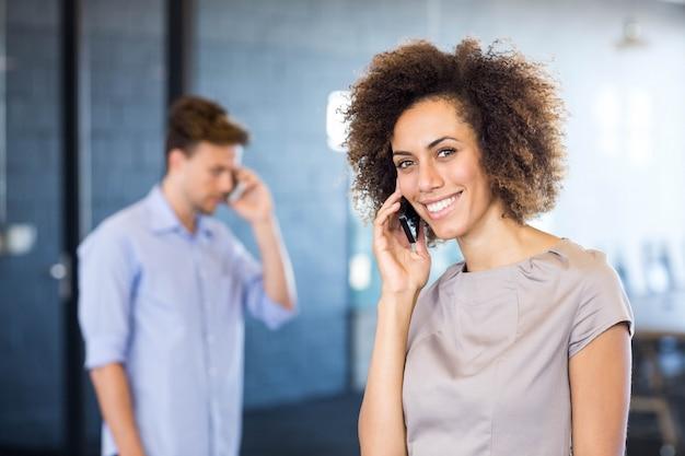 Mulher jovem, comunicando, ligado, telefone móvel, frente, sala conferência, em, escritório