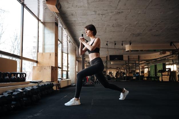Mulher jovem concentrada fitness malhando e fazendo agachamentos no ginásio