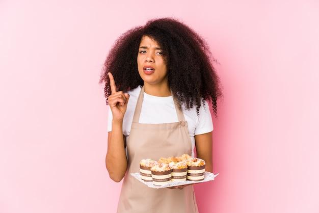 Mulher jovem confeiteiro afro segurando cupcakes