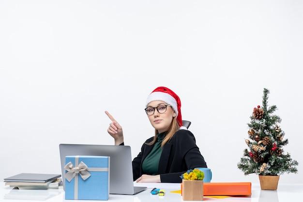 Mulher jovem confiante com chapéu de papai noel e óculos, sentada à mesa com uma árvore de natal e um presente nela.