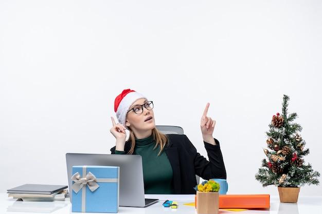 Mulher jovem confiante com chapéu de papai noel sentada a uma mesa com uma árvore de natal e um presente e apontando para cima no lado esquerdo em fundo branco