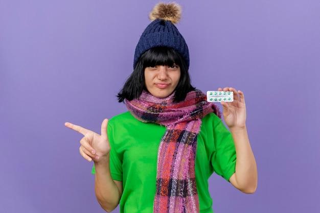 Mulher jovem confiante e doente com chapéu e lenço de inverno, olhando para a frente, segurando o pacote de cápsulas apontando para o lado isolado na parede roxa com espaço de cópia
