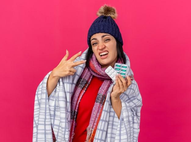 Mulher jovem confiante e doente usando chapéu de inverno e lenço embrulhado em uma manta segurando pacotes de pílulas médicas olhando para a frente, mostrando três com a mão isolada na parede rosa