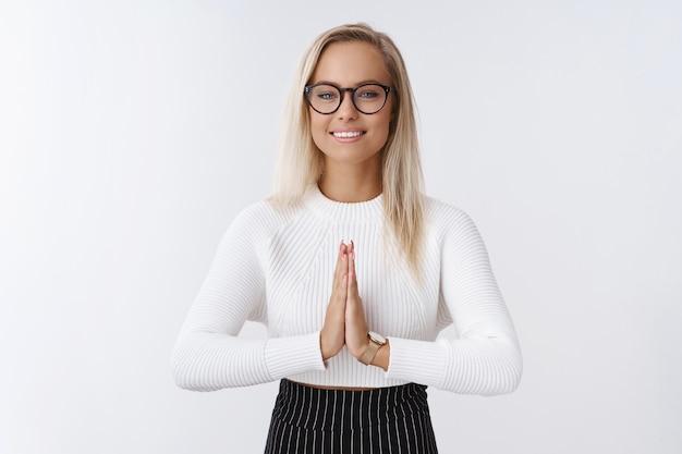 Mulher jovem confiante e feliz, de boa aparência, com cabelo loiro em copos, segurando as palmas das mãos juntas em pray ou namaste, sentindo-se aliviado e fresco após a meditação ou sedativo sobre uma parede branca.