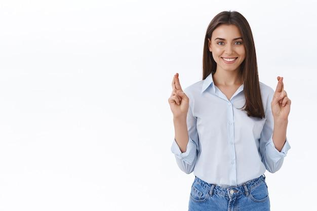 Mulher jovem confiante e otimista esperançosa cruza os dedos para dar boa sorte, acredita que tudo está bem, rezando para que o sonho de boa vontade se torne realidade, olhando para a câmera e sorrindo como se quisesse cumprir