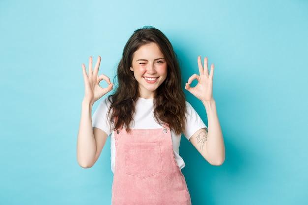 Mulher jovem confiante e positiva, piscando e sorrindo, mostrando sinais de aprovação, diga sim, dê aprovação, elogie o bom trabalho, em pé contra um fundo azul.