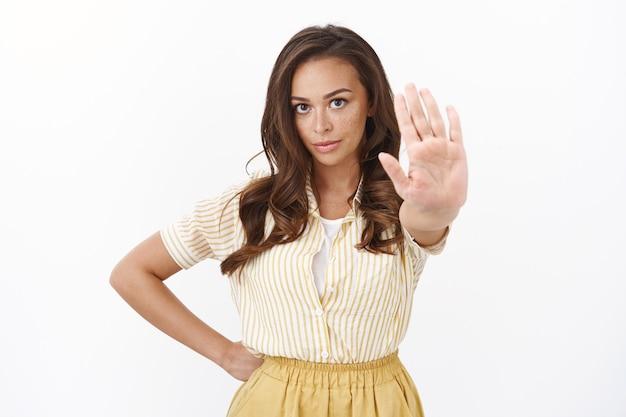 Mulher jovem confiante e séria mostrando sinal de invasão, estende a mão em direção à câmera e parece desapontada, dizendo não, exigindo virar as costas, rejeitar um convidado desagradável