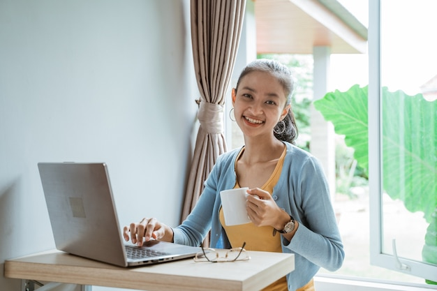 Mulher jovem confiante em roupa casual inteligente trabalhando em um laptop enquanto está sentado perto da janela em casa