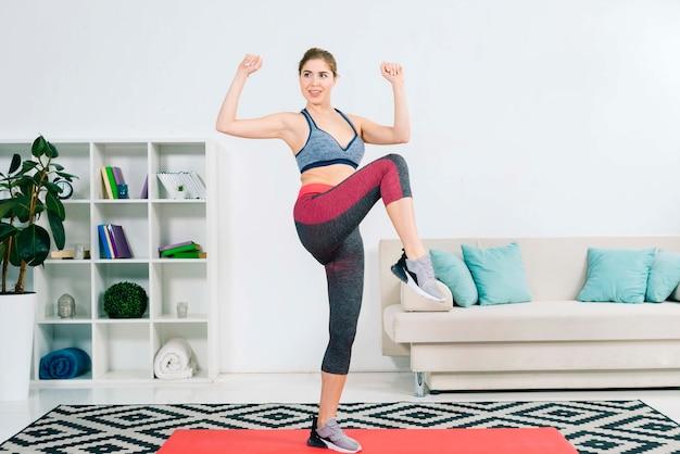 Mulher jovem confiante fazendo exercício no tapete na sala de estar