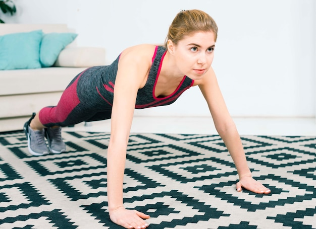 Mulher jovem confiante fazendo flexões no tapete na sala de estar
