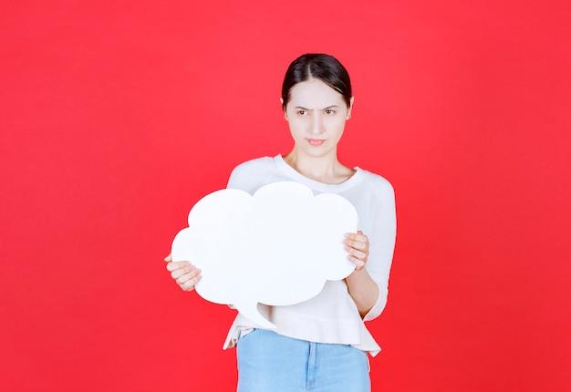 Mulher jovem confiante segurando um balão com uma forma de nuvem