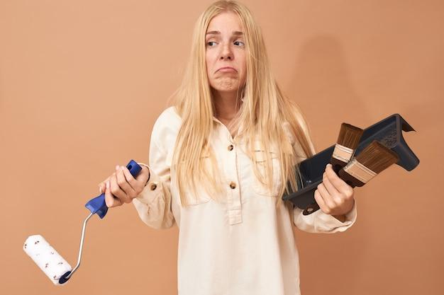 Mulher jovem confusa, com cabelo longo e liso, posando em um espaço em branco, segurando ferramentas especiais, enquanto pinta paredes