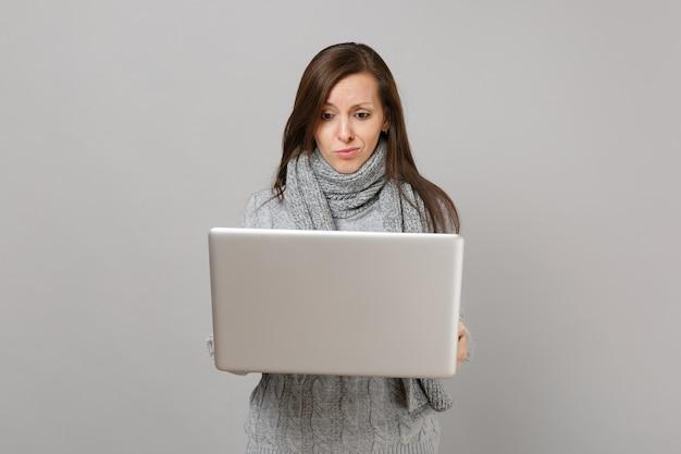 Mulher jovem confusa de suéter cinza, lenço trabalhando no computador laptop pc isolado no fundo da parede cinza. estilo de vida saudável, consultoria de tratamento online, conceito de estação fria. simule o espaço da cópia.