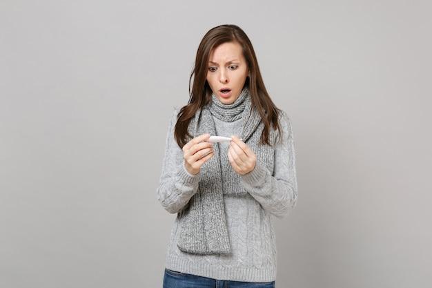 Mulher jovem confusa de suéter cinza, segurando o lenço, olhando no termômetro isolado no fundo da parede cinza. estilo de vida saudável, tratamento de doença doente, conceito de estação fria. simule o espaço da cópia.
