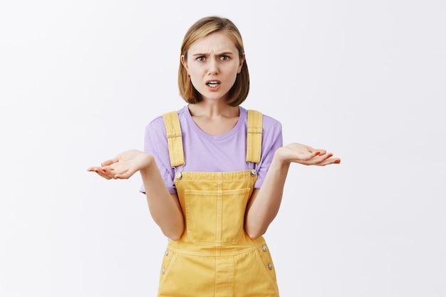 Mulher jovem confusa e incomodada franzindo a testa, encolhendo os ombros e espalhando as mãos para os lados, perplexa