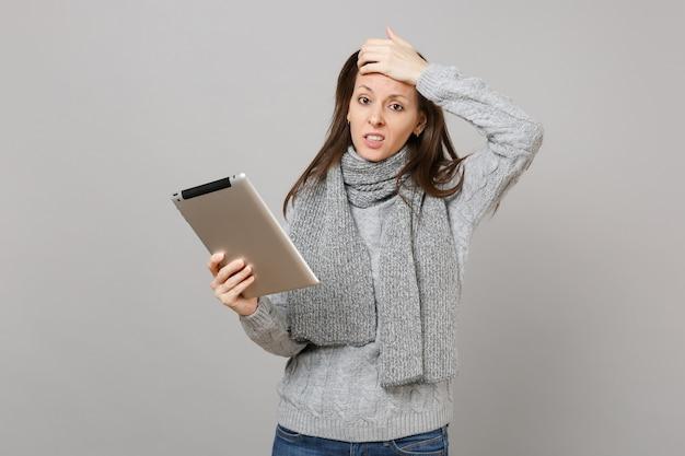 Mulher jovem confusa em uma camisola, lenço colocado a mão na cabeça usando computador tablet pc isolado em fundo cinza. estilo de vida saudável, consultoria de tratamento online, conceito de estação fria. simule o espaço da cópia.