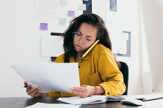 Mulher jovem confusa lendo documentos e discutindo ao telefone