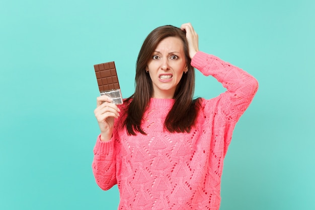 Mulher jovem confusa na camisola de malha rosa, colocando a mão na cabeça, segurando a barra de chocolate isolada no fundo da parede azul turquesa, retrato de estúdio. conceito de estilo de vida de pessoas. simule o espaço da cópia.