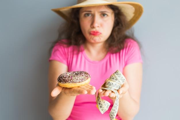 Mulher jovem confusa segurando um donut e uma fita métrica. conceito de doces, junk food insalubre e obesidade.