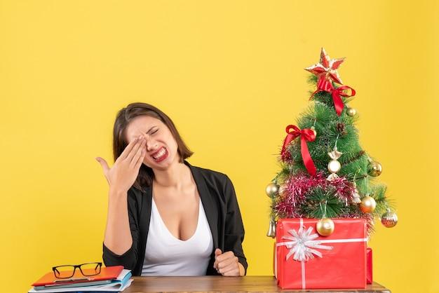 Mulher jovem confusa sentada à mesa em um terno perto da árvore de natal decorada no escritório em amarelo
