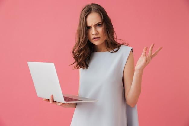 Mulher jovem confusa usando o computador portátil.