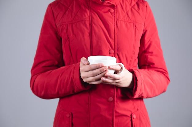 Mulher jovem congelada com uma xícara de chá