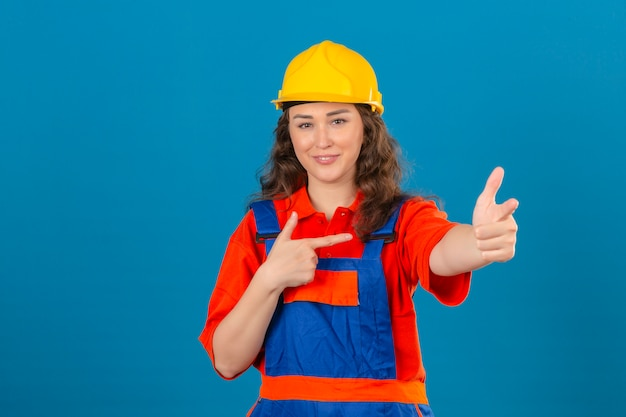 Mulher jovem construtor em uniforme de construção e capacete de segurança com sorriso no rosto, apontando com as mãos e os dedos para o lado ao longo da parede azul isolada