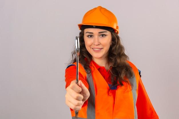 Mulher jovem construtor em uniforme de construção e capacete de segurança em pé com chave, mostrando a câmera sorrindo amigável sobre parede branca isolada