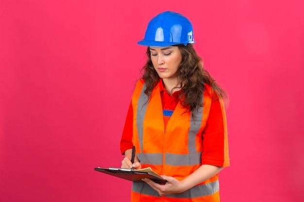 Mulher jovem construtor em uniforme de construção e capacete de segurança em pé com prancheta fazendo anotações com cara séria sobre parede rosa isolada