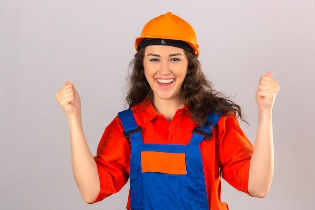 Mulher jovem construtor em uniforme de construção e capacete de segurança feliz e animado comemorando a vitória expressando grande sucesso, levantando os punhos sobre parede branca isolada