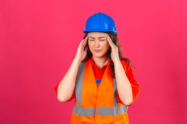 Mulher jovem construtor em uniforme de construção e capacete de segurança, olhando mal tocando sua cabeça com forte dor de cabeça sobre parede rosa isolada
