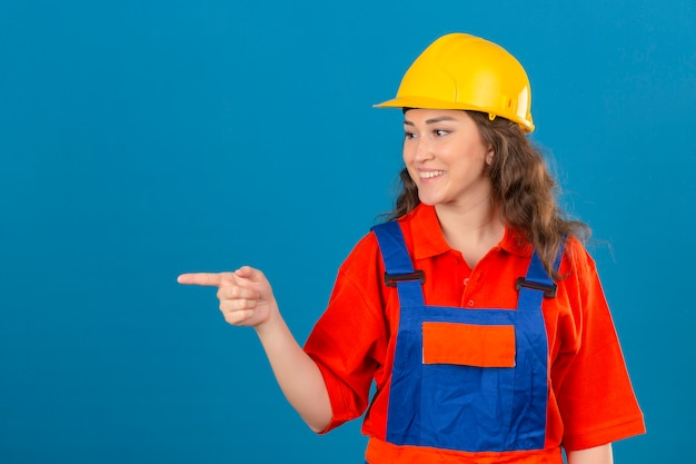 Mulher jovem construtor em uniforme de construção e capacete de segurança sorrindo alegremente olhando confiante apontando com o dedo indicador para o lado sobre parede azul isolada