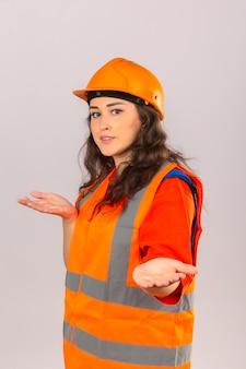Mulher jovem construtor em uniforme de construção e capacete de segurança, sorrindo, fazendo um gesto de boas-vindas sobre parede branca isolada