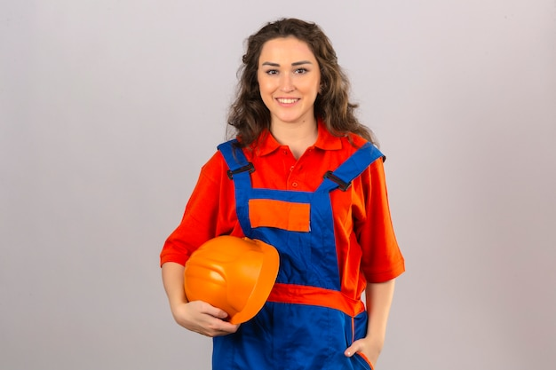 Mulher jovem construtor em uniforme de construção permanente com capacete de segurança nas mãos sorrindo amigável sobre parede branca isolada