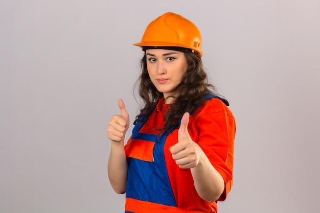 Mulher jovem construtor no uniforme de construção e capacete de segurança com sorriso aparecendo polegares sobre parede branca isolada