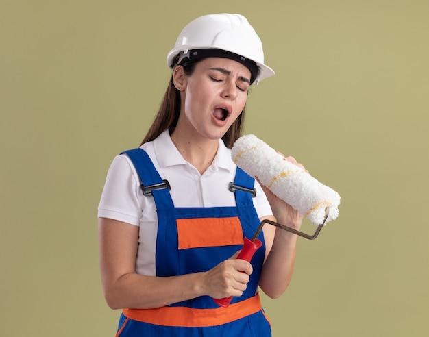Mulher jovem construtora com os olhos fechados, uniformizada, segurando a escova giratória e cantando, isolada na parede verde oliva