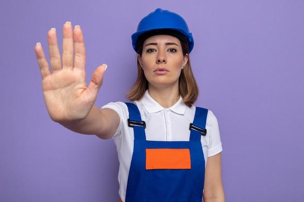 Mulher jovem construtora com uniforme de construção e capacete de segurança com cara séria, fazendo gesto de parada com a mão em pé sobre a parede roxa