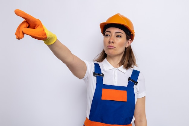 Mulher jovem construtora com uniforme de construção e capacete de segurança com luvas de borracha, olhando para o lado com uma cara séria apontando com o dedo indicador para algo em pé no branco
