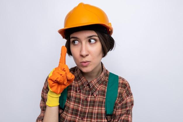 Mulher jovem construtora com uniforme de construção e capacete de segurança com luvas de borracha, olhando para o lado com uma cara séria, mostrando o dedo indicador em pé sobre uma parede branca