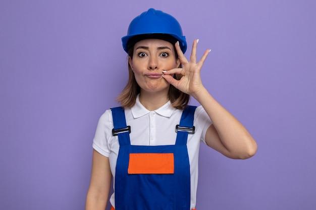 Mulher jovem construtora com uniforme de construção e capacete de segurança fazendo gesto de silêncio como fechar a boca com um zíper em pé sobre a parede roxa