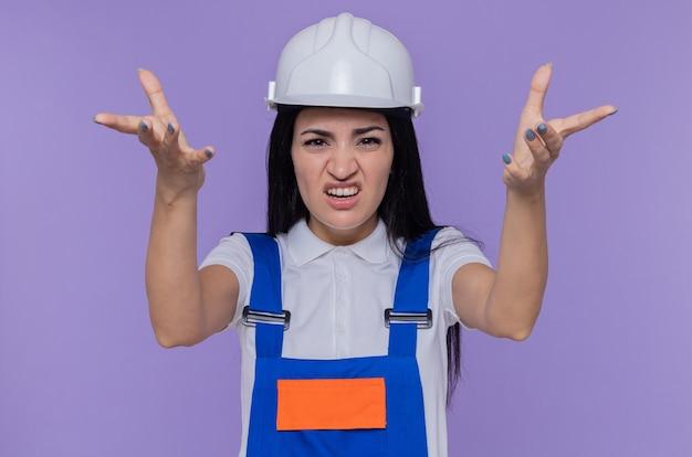 Mulher jovem construtora com uniforme de construção e capacete de segurança olhando para a frente com os braços levantados, como se estivesse discutindo em pé sobre a parede roxa