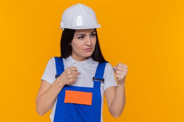 Mulher jovem construtora com uniforme de construção e capacete de segurança olhando para o lado com expressão séria e confiante com o punho cerrado como um lutador em pé sobre a parede laranja