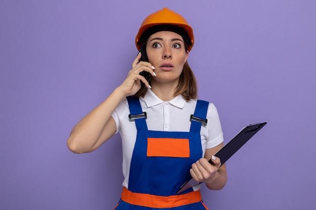 Mulher jovem construtora com uniforme de construção e capacete de segurança segurando a prancheta e parecendo preocupada enquanto fala ao telefone celular em pé sobre a parede roxa