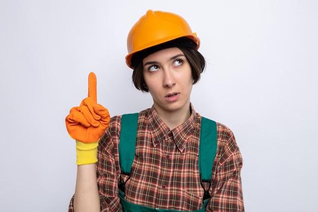 Mulher jovem construtora em uniforme de construção e capacete de segurança em luvas de borracha, olhando para cima com uma cara séria, mostrando o dedo indicador tendo uma nova ideia em pé sobre uma parede branca