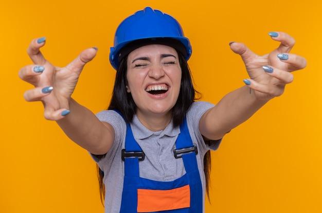 Mulher jovem construtora em uniforme de construção e capacete de segurança levantando os braços loucamente louca, gritando com expressão agressiva em pé sobre a parede laranja