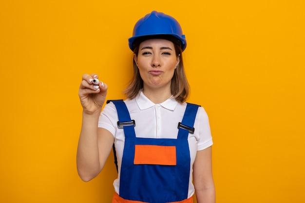 Mulher jovem construtora em uniforme de construção e capacete de segurança olhando com um sorriso no rosto escrevendo com uma caneta no ar